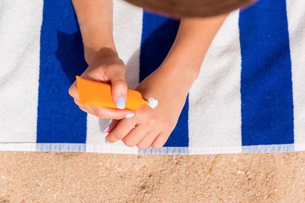 美しい女性がビーチの砂の上のタオルで日光浴をしていて、日焼け止めで手を保護しています。