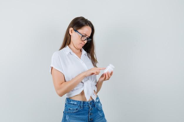 Bella signora guardando la bottiglia di pillole in camicetta bianca, occhiali e guardando attento. vista frontale.