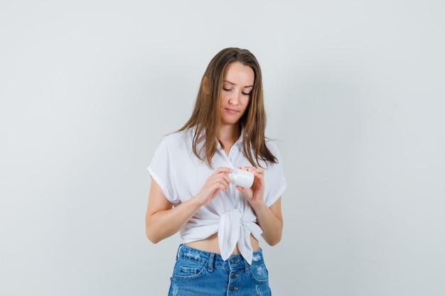 Bella signora guardando la bottiglia di pillole in camicetta bianca, jeans e guardando attento, vista frontale.