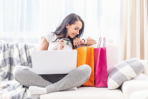 Beautiful lady looking into colorful paper shopping bags next to her smiling, with a laptop on her criss crossed legs and a payment card in her hand in a light living room.