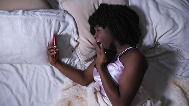 美しい女性は、現代のスマートフォンのディスプレイとあくびを見て