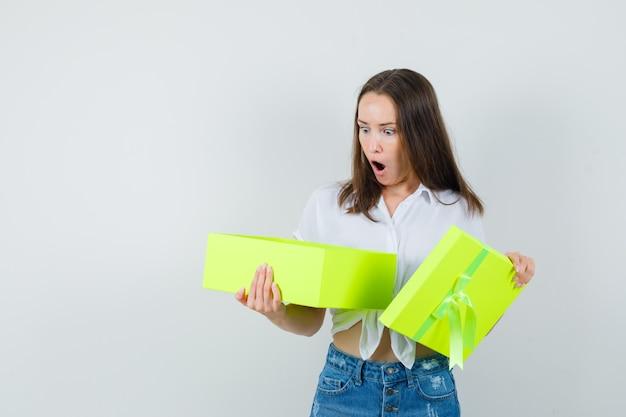 흰 블라우스, 청바지에 선물 상자를 열고 놀랍게도, 전면보기를보고 아름다운 아가씨. 텍스트를위한 공간