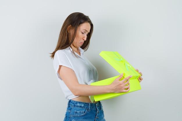 白いブラウスで黄色のギフトボックスを開き、興味を持っているように見える美しい女性。正面図。