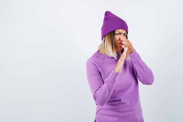 Красивая дама зажимает нос, не демонстрирует жестов в свитере, шапочке и выглядит недовольно. передний план.