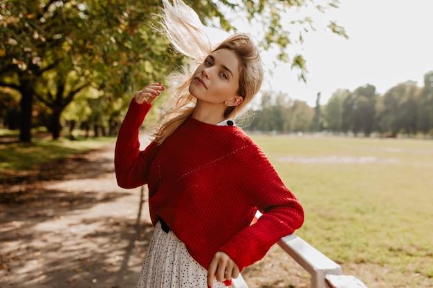 屋外で髪をいじっている美しい女性。木々の下で喜んでポーズをとる若いブロンドの女性。
