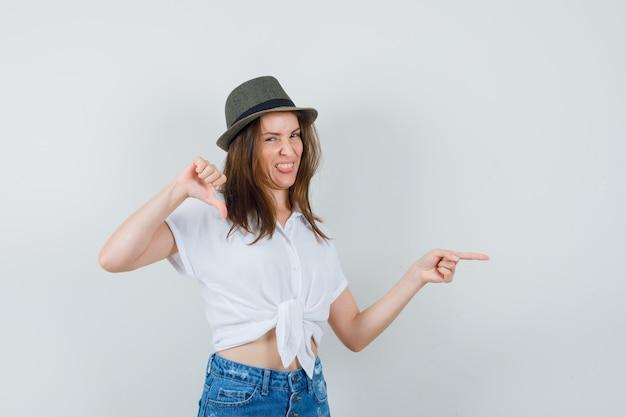 흰색 블라우스, 모자, 전면보기에서 아래로 엄지 손가락을 보여주는 동안 옆으로 가리키는 아름 다운 아가씨.