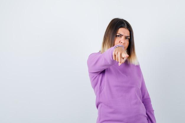 아름 다운 아가씨 스웨터에 카메라를 가리키고 결정 찾고. 전면보기.