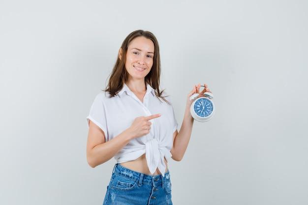 白いブラウスの正面図で時計を指している美しい女性。