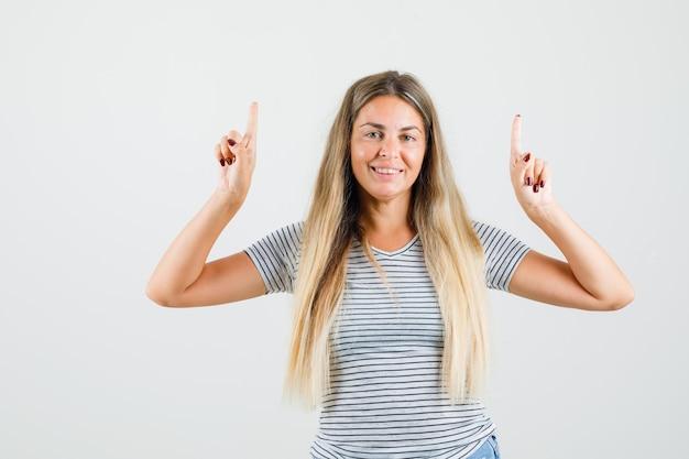Tシャツで上向きに幸せそうに見える美しい女性。正面図。