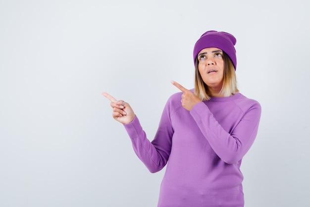 Bella signora che punta all'angolo in alto a sinistra in maglione, berretto e sembra sicura. vista frontale.