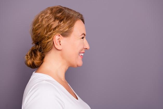 紫色の壁に向かってポーズをとる美しい女性
