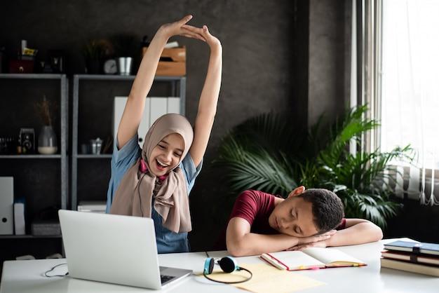 Красивая дама поднимает руки в воздухе со счастливым чувством после выполнения домашнего задания