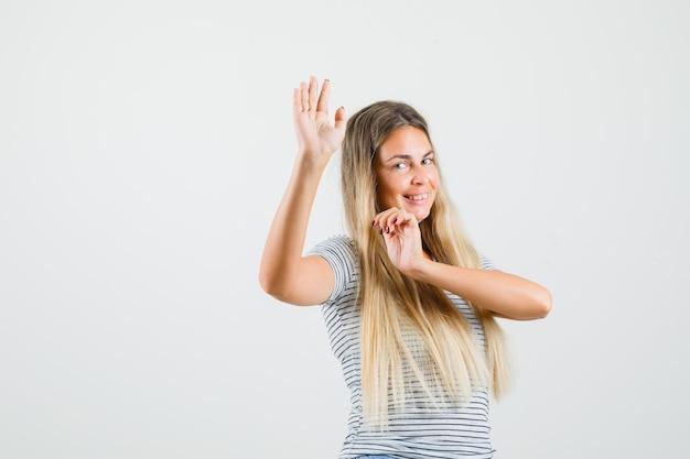Bella signora alzando le mani mentre balla in t-shirt e sembra divertita, vista frontale.