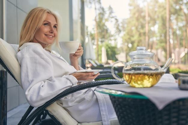 휴가 아침에 차를 마시는 동안 리조트에서 쉬고 아름다운 아가씨