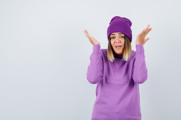 Beautiful lady showing helpless gesture in sweater, beanie and looking helpless . front view.