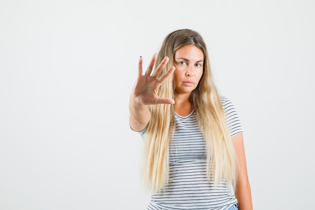 Красивая дама показывает жест остановки в футболке и выглядит серьезно. передний план.
