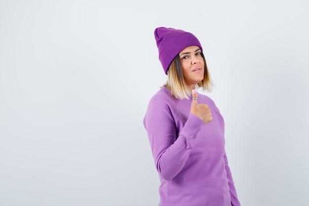 Bella signora che mostra pollice in su in maglione, berretto e sembra sicura, vista frontale.
