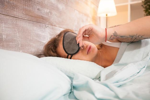 寝室の枕に頭とアイカバーで寝ている美しい女性。