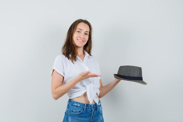 白いブラウス、帽子で彼女の帽子を見せるために手のひらを広げている美しい女性。