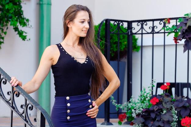 開いたドアの近くの家のポーチに立っている美しい女性