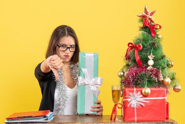 Bella signora in vestito con gli occhiali che mostra il suo regalo facendo un gesto negativo e seduto a un tavolo con un albero di natale su di esso in ufficio