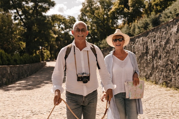 Bella signora in occhiali da sole, cappello e camicetta a righe sorridente e in posa con l'uomo con i baffi in camicia bianca e jeans con la macchina fotografica all'aperto.