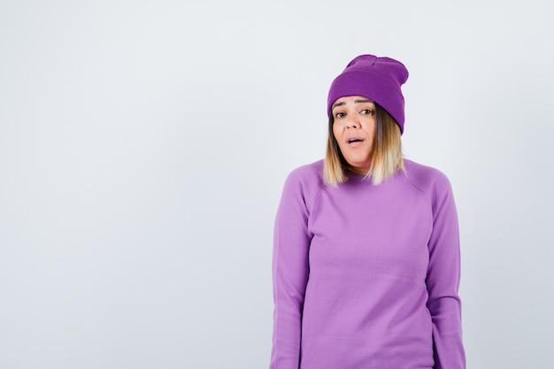 Bella signora in maglione, berretto in posa in piedi, aprendo la bocca e guardando sorpreso, vista frontale.