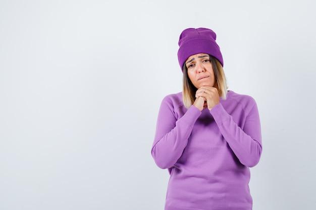 Bella signora in maglione, berretto con le mani sotto il mento e guardando speranzoso, vista frontale.