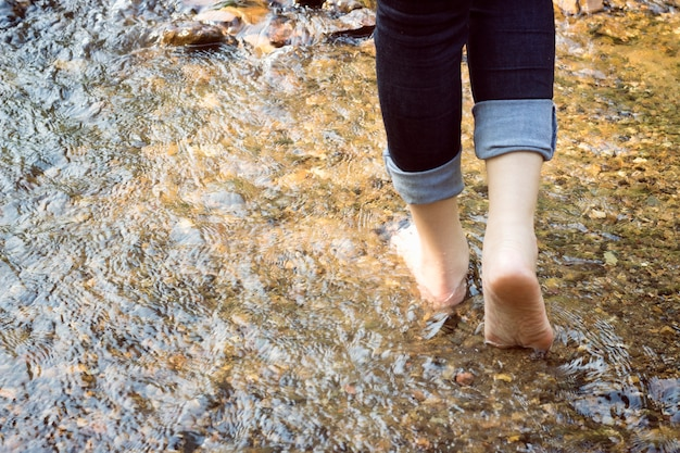 Beautiful lady that wear jeans is walking on the stones in river.
