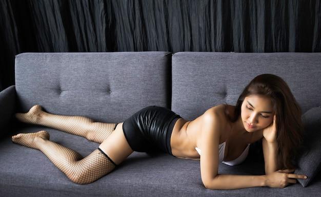 Beautiful lady wearing little bra , laying down on sofa, portrail model posing, sexy woman