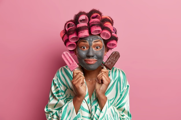 Beautiful lady wearing mask for face care wearing hair curlers isolated