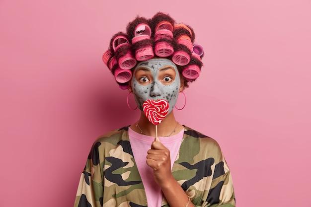 Bella signora che indossa la maschera per la cura del viso indossando bigodini isolati