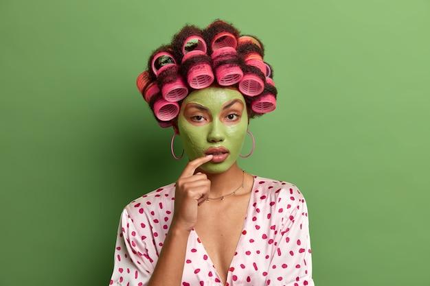 고립 된 머리카락 curlers를 입고 얼굴 관리를 위해 마스크를 쓰고 아름다운 아가씨