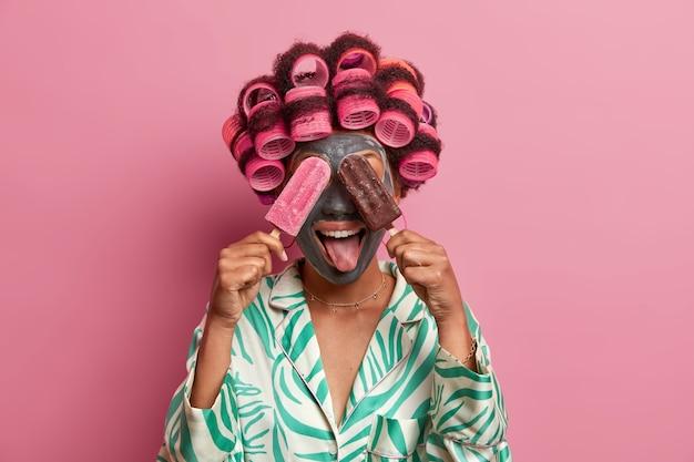 隔離されたヘアカーラーを身に着けているフェイスケアのためのマスクを身に着けている美しい女性
