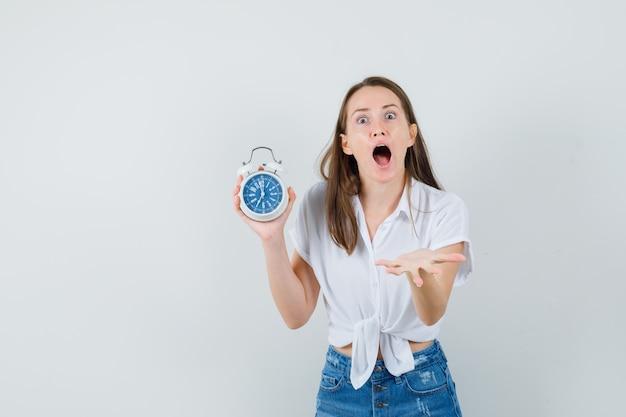 Bella signora in camicetta bianca che tiene orologio mentre urla e sembra allarmata, vista frontale.