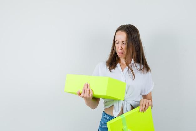Bella signora in camicetta bianca, jeans guardando dentro la scatola gialla, vista frontale.