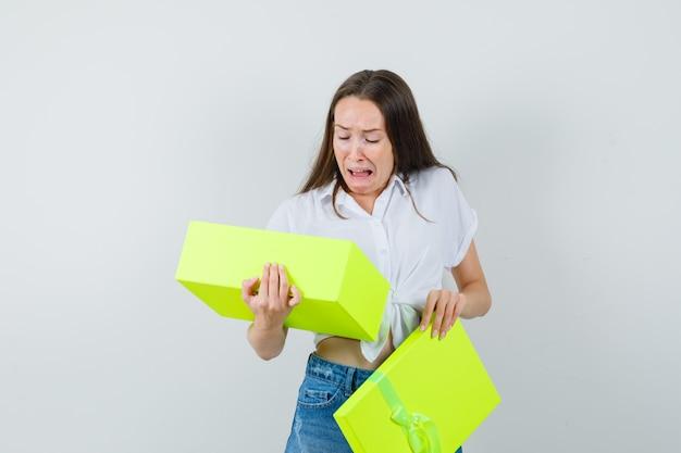 Bella signora in camicetta bianca, jeans guardando dentro la scatola gialla e guardando disgustato, vista frontale.