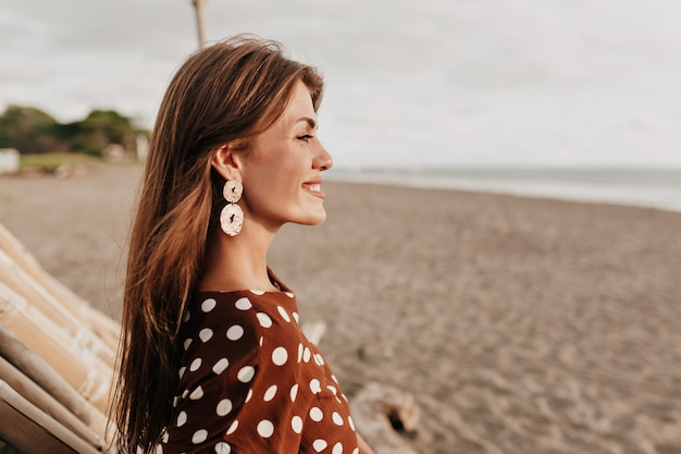 햇빛에 낭만적 인 미소로 바다를 바라 보는 해외 부드러운 미소로 아름다운 아가씨