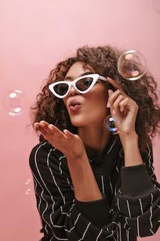 キスを吹いてピンクの壁に泡でポーズをとる縞模様の黒い服を着た巻き毛のブルネットの髪を持つ美しい女性。