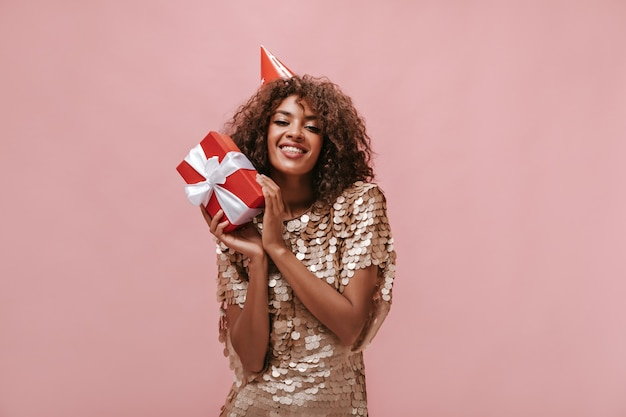 美丽的女士卷发在米色的裙子和假日帽微笑,拿着红色的礼品盒在孤立的粉红色墙壁..
