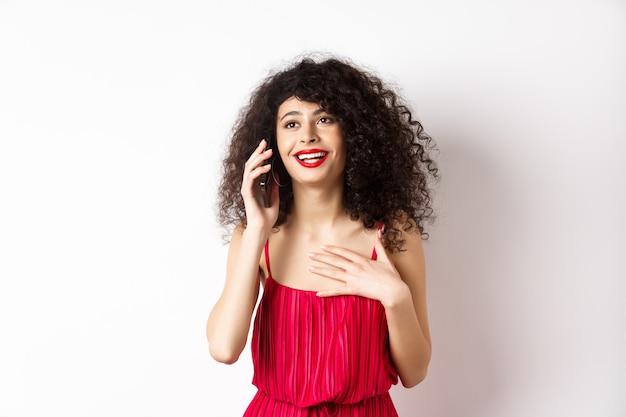 巻き毛、赤いドレスを着て、電話で話している、幸せそうな顔、楽しい会話をしている、白い背景の上に立っている美しい女性。