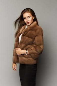 バックグラウンドで分離された豪華な毛皮のコートでエレガントなヘアスタイルを持つ美しい女性。ファッション人工毛皮。高級毛皮のコートで美しい女性。