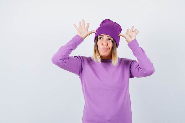 Bella signora con le mani vicino alla testa come orecchie in maglione, berretto e dall'aspetto divertente, vista frontale.