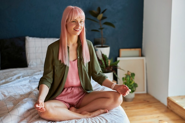 緑のシャツを着た長い髪の美しい女性は、ベッドの上の蓮華座で瞑想します