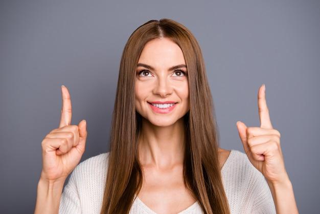 灰色の壁にポーズをとって長い髪の美しい女性