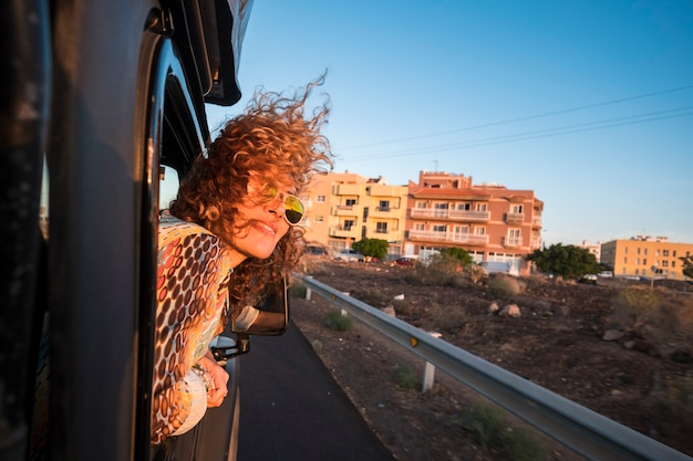素敵な笑顔の美しい女性は、夕日の太陽を見て黒い車で旅行します