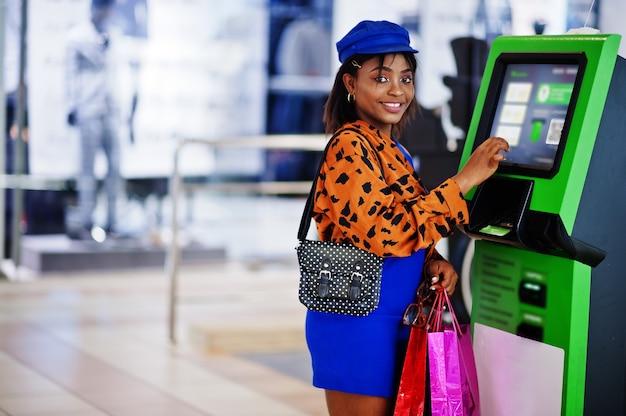 Красивая дама с сумками для покупок в торговом центре принимает наличные в банкомате