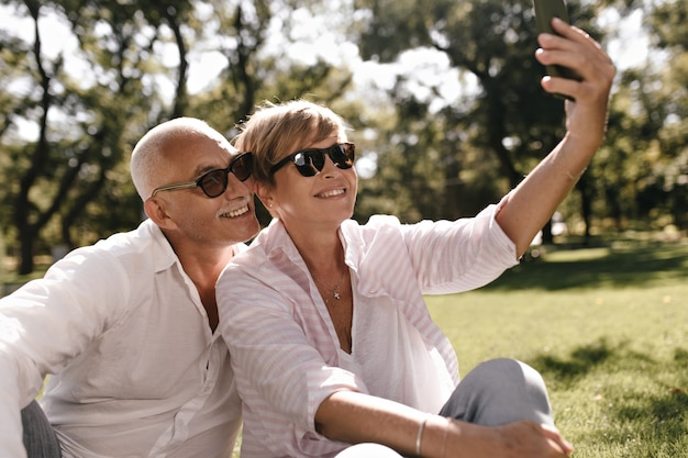 Beautiful lady with short hair in sunglasses, pink blouse and jeans sitting on grass and making photo with grey haired man in white outfit on park.