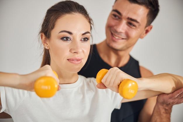 잘생긴 남자가 그녀를 보고 있는 동안 운동하는 아름다운 여자