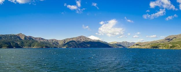美しい湖と青い空の下の山